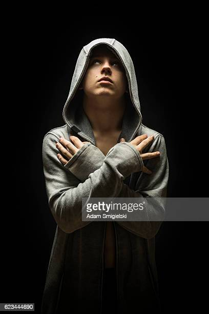teenage boy dressed in hooded jacket in the dark