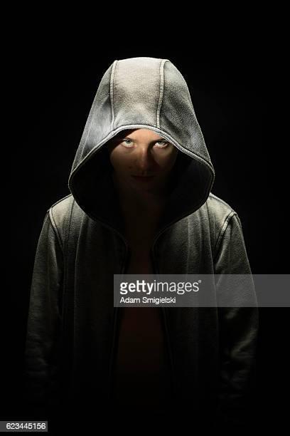 teenage boy dressed in hooded jacket in the dark