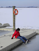 Teenage boy dressed in winter clothing sitting on a dock on frozen water. The boy dangles his feet over the edge touching the ice with his feet. The boy stares at the ice as if dreaming of Summer and
