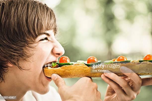 Teenage boy eating a sandwich
