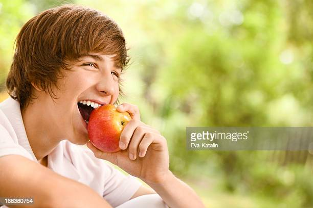 Teenage boy eating an apple