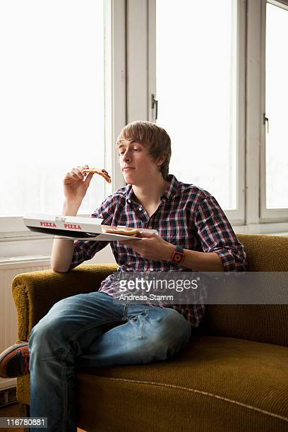 A teenage boy eating delivery pizza