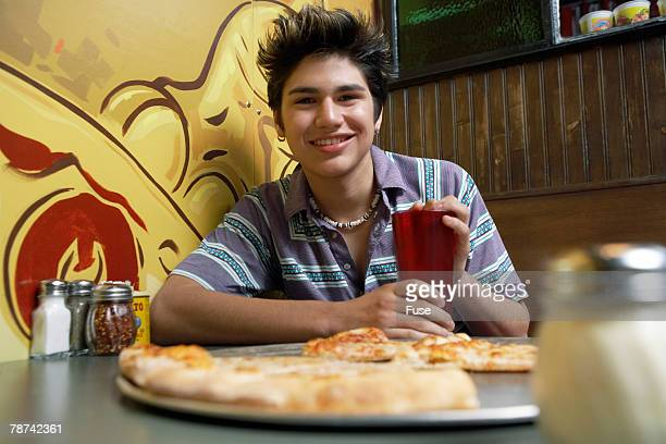 Teenage Boy Eating Pizza at Cafe
