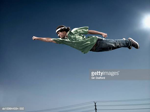 Teenage boy (16-17) flying in mid air, low angle view