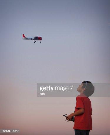 Teenage boy flying remote controlled aeroplane