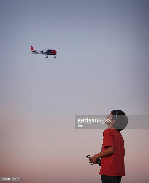 Teenage boy flying remote controlled aeroplane
