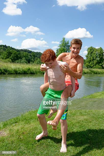 Teenage boy giving his friend a piggy back ride