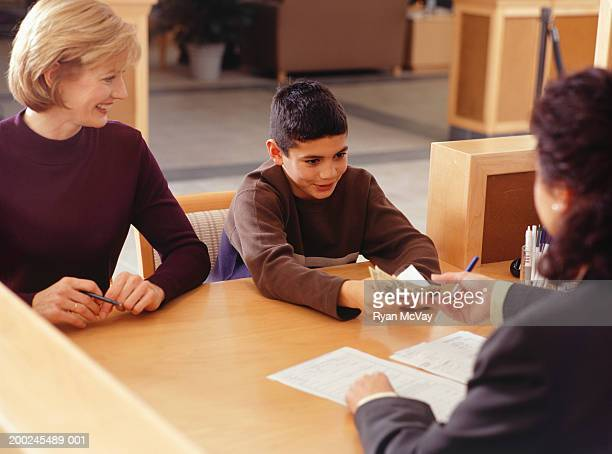 Teenage boy (13-14) giving money to bank teller
