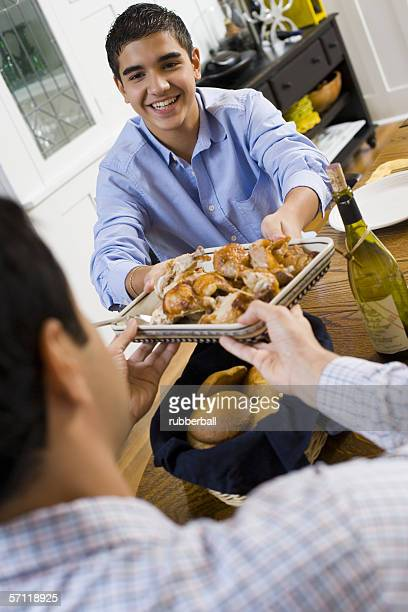 Teenage boy handing a plate of roasted chicken to his father