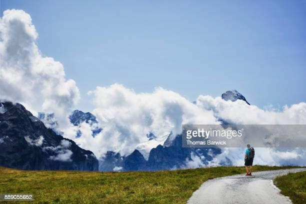 Teenage boy hiking along path looking at peaks in Swiss Alps