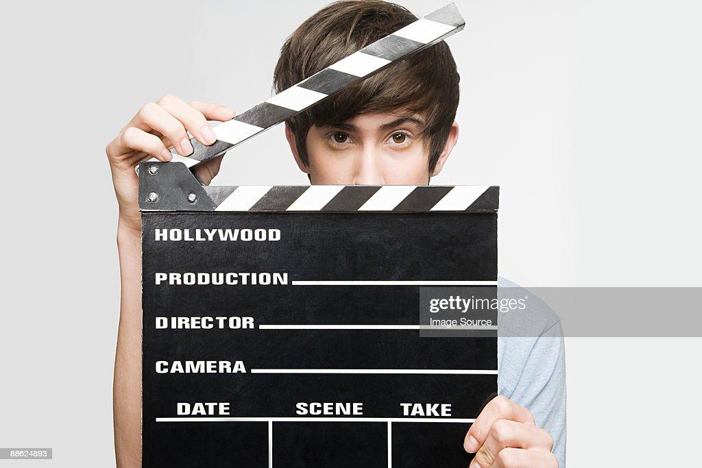 Teenage boy holding a clapperboard