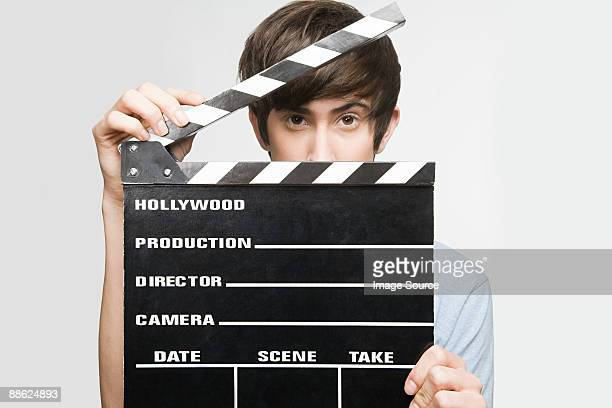 Teenage boy holding a clapperboard
