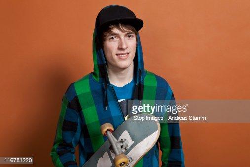 A teenage boy holding a skateboard, portrait, studio shot