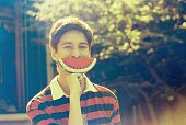Teenage boy holding artificial watermelon