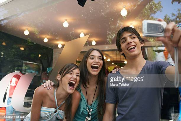 Teenage boy (14-16) holding camera phone by two young women smiling
