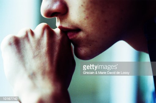 Teenage boy (16-18) holding fist to mouth, close-up, section : Stock Photo