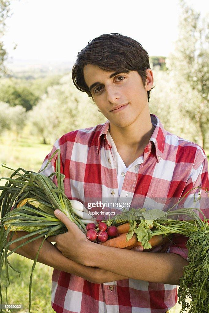 Teenage boy holding fresh produce , Italy : Stock Photo