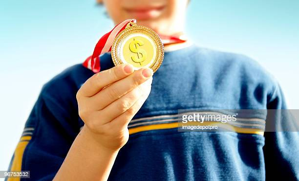 teenage boy holding gold medal