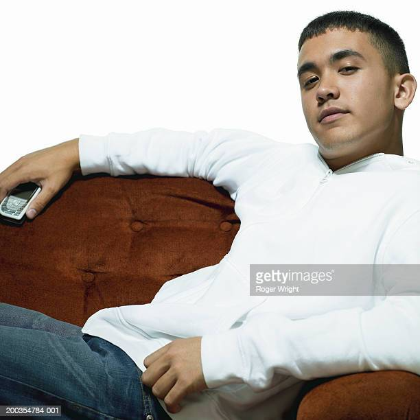 Teenage boy (16-18) holding mobile phone reclining on sofa, portrait