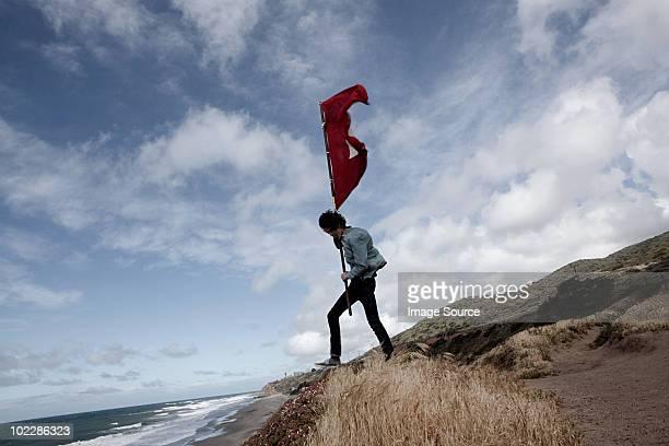 Menino adolescente segurando bandeira vermelha