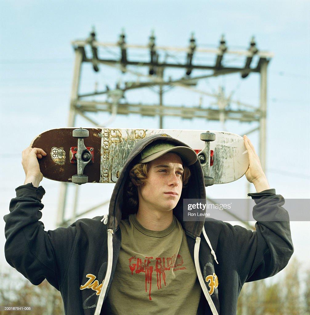 Teenage boy (16-18) holding skateboard behind head : Stock Photo