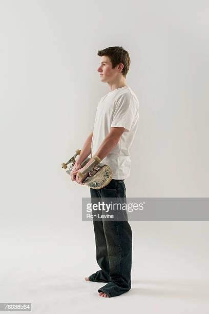 Teenage boy (14-15) holding skateboard, side view