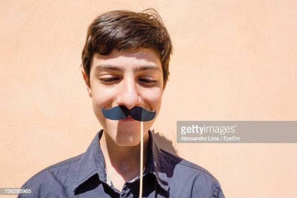 Teenage Boy Holding Stick With Mustache Against Wall
