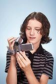 Teenage boy (13-15) holding video camera, looking at display screen