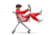 Teenage boy in a racing suit with VR googled holding a steering wheel inside a shopping cart isolated on white background