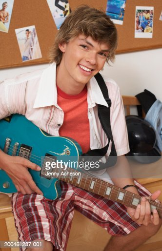 Teenage boy (16-18) in bedroom, holding guitar, smiling, portrait : Stock Photo