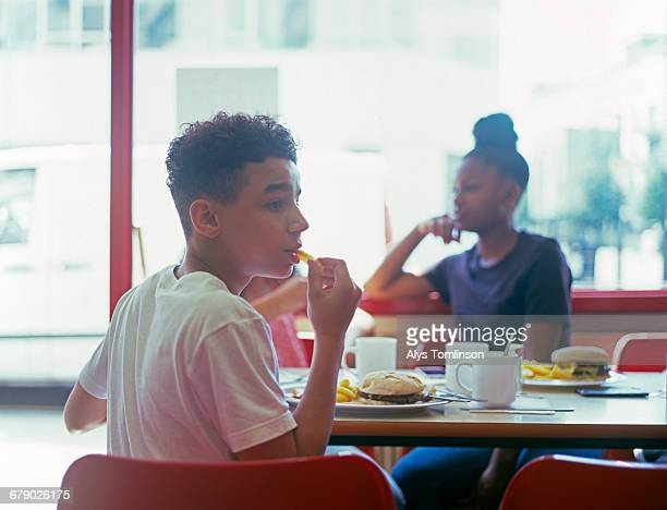 Teenage boy in cafe eating burger and chips