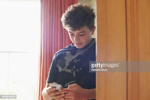 Teenage boy in his bedroom texting on smartphone