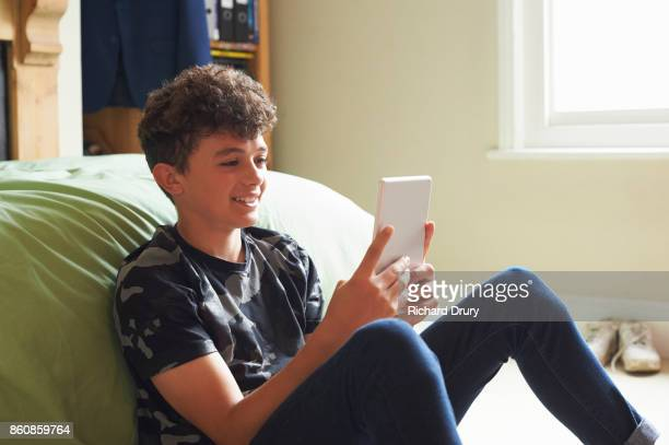 Teenage boy in his bedroom using digital tablet