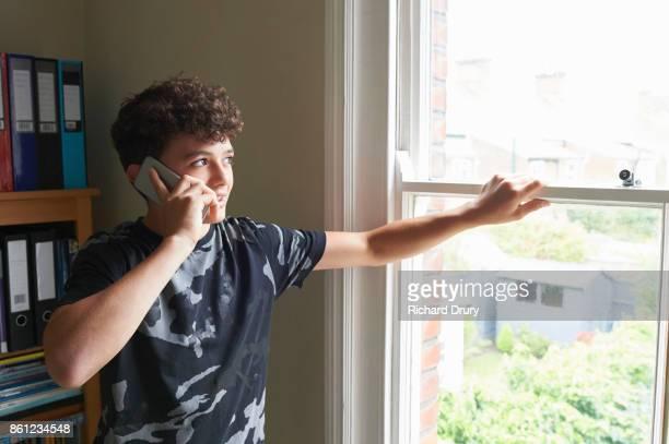 Teenage boy in his bedroom using phone