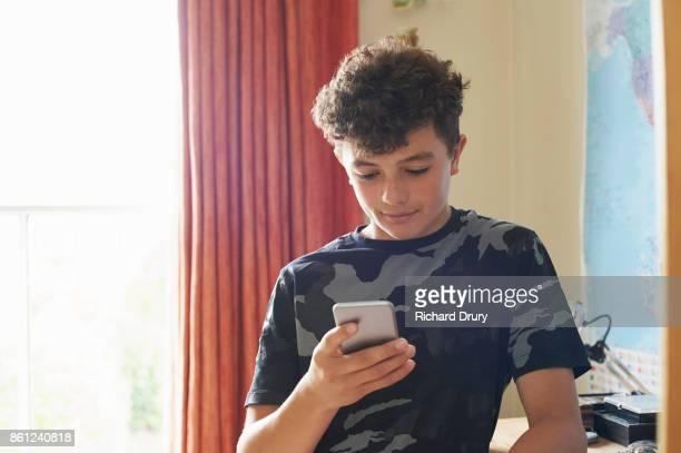 Teenage boy in his bedroom using smartphone
