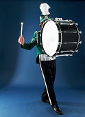 Teenage boy (13-15) in marching band uniform playing bass drum
