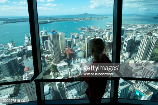 Teenage boy (12-14) in Sky Tower looking out at cityscape, rear view