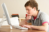 Teenage Boy in Thought Studying at Home