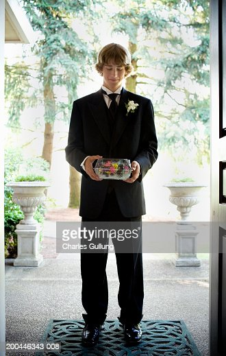 Teenage boy (14-16) in tuxedo holding corsage on front porch