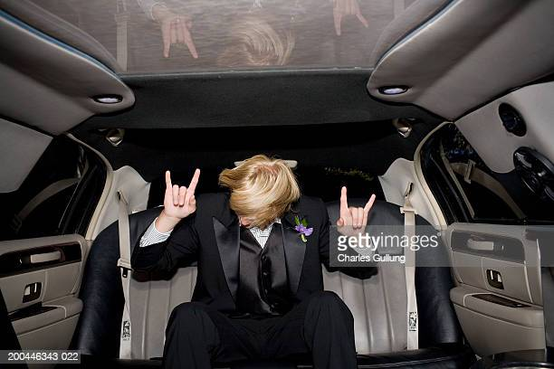 Teenage boy (15-17) in tuxedo riding in limousine, gesturing