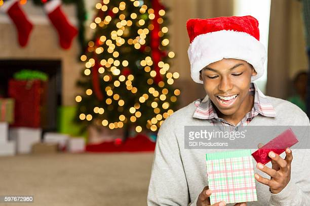 Teenage boy is surprised while opening Christmas gift