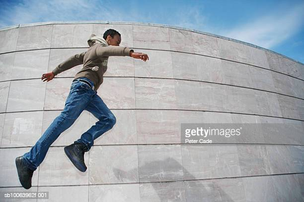 Teenage boy (14-15) jumping in front of stone wall, low angle view