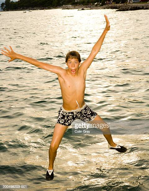 Teenage boy (13-14) jumping into water