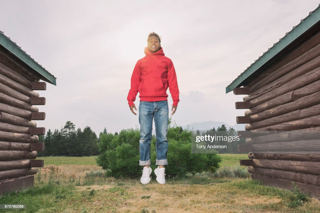 Teenage boy jumping outdoors between two cabins