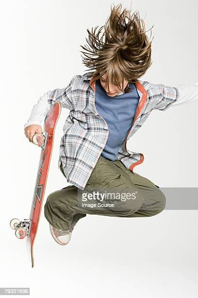 A teenage boy jumping with skateboard