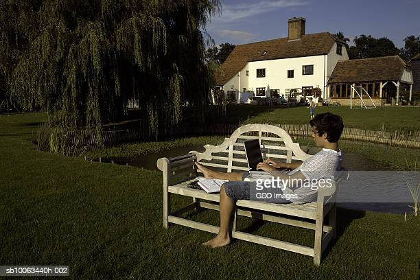 Teenage boy (14-15) leaning on beck using laptop, house in background