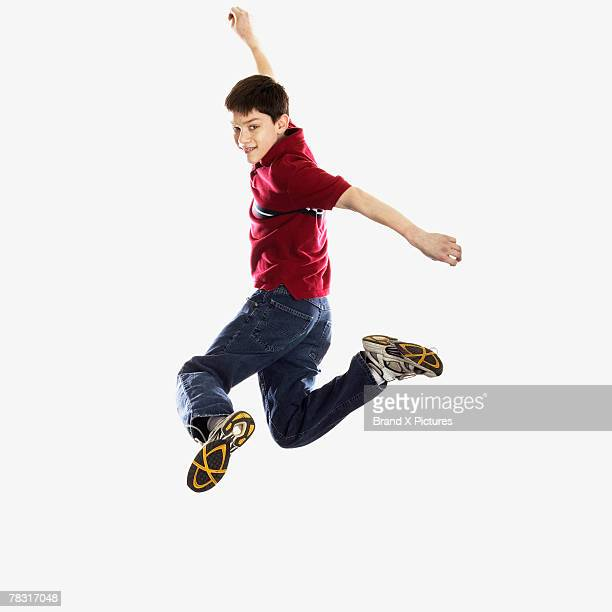 Teenage boy leaping into air