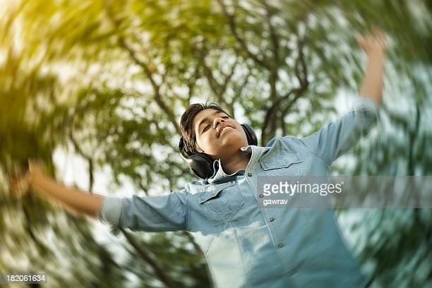 Teenage boy listening music and dancing under trees