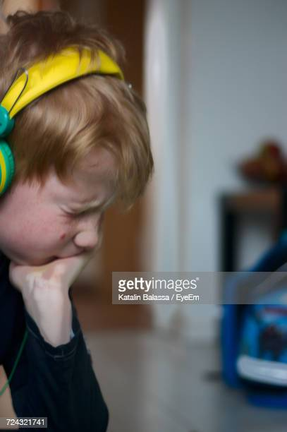 Teenage Boy Listening Music With Headphones At Home