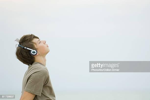 Teenage boy listening to headphones, looking up, side view